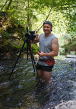 Professional photographer with camera on tripod. In the middle of a cold river Royalty Free Stock Image