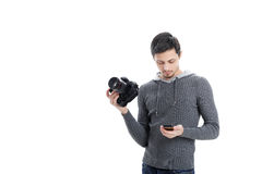 Professional photographer with DSLR digital camera looking phone Royalty Free Stock Photos