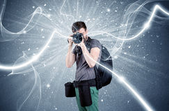 Professional photographer with dynamic lines. A young amateur photographer with professional photographic equipment taking picture in front of blue wall with Stock Image