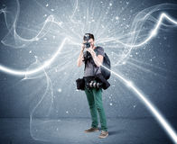 Professional photographer with dynamic lines. A young amateur photographer with professional photographic equipment taking picture in front of blue wall with Royalty Free Stock Image