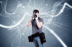 Professional photographer with dynamic lines. A young amateur photographer with professional photographic equipment taking picture in front of blue wall with Royalty Free Stock Photo