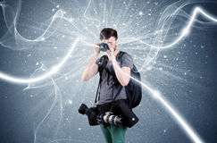 Professional photographer with dynamic lines. A young amateur photographer with professional photographic equipment taking picture in front of blue wall with Stock Photography