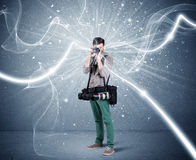Professional photographer with dynamic lines. A young amateur photographer with professional photographic equipment taking picture in front of blue wall with Stock Photo