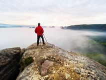 Professional photographer and hiker shooting in wild nature with a digital camera and a tripod. View over clouds to morning horizon Royalty Free Stock Photos