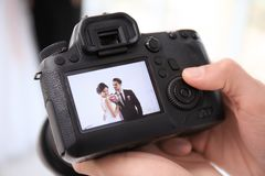 Professional photographer holding camera with lovely wedding couple on display Royalty Free Stock Image