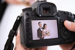 Professional photographer holding camera with lovely wedding couple Stock Photo