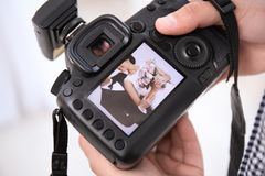 Professional photographer holding camera. With lovely wedding couple on display, closeup Stock Photos