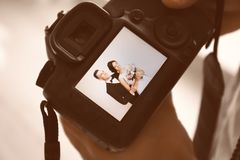 Professional photographer holding camera. With lovely wedding couple on display, closeup Royalty Free Stock Photos