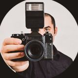 Professional photographer holding old, retro film camera and fla Stock Images