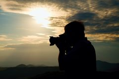Professional photographer in jeans and shirt  takes photos with mirror camera on peak of rock. Dreamy landscape, orange  Sun at ho Royalty Free Stock Image