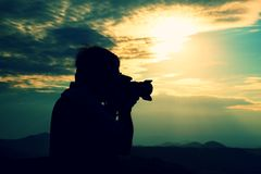 Professional photographer in jeans and shirt  takes photos with mirror camera on peak of rock. Dreamy landscape, orange  Sun at ho Stock Image