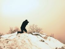 Professional photographer lay down to snow and takes photos with mirror camera on peak. Of snowy rock. . Man lay with big mirror camera on neck. Snowy rocky Royalty Free Stock Photos