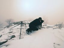 Professional photographer lay down to snow and takes photos with mirror camera on peak. Of snowy rock. . Man lay with big mirror camera on neck. Snowy rocky Stock Photo