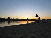 Professional Photographer Photo Session with Just Married Newly-Wed Couple on Beach during Sunset stock photo