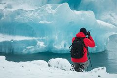 Professional photographer in red coat and black backpack taking picture of glacier ice. A photographer taking a knee behind their tripod and digital slr camera royalty free stock photography