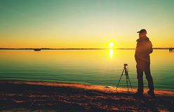 Professional photographer shoot sunset with camera on tripod. Professional photographer shooting sunset with wide lens, camera and tripod at the beach work stock photography