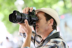 Professional photographer shooting outdoors. Professional photographer in town taking pictures Royalty Free Stock Photos