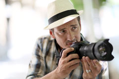 Professional photographer shooting. Professional photographer in town taking pictures Royalty Free Stock Photo