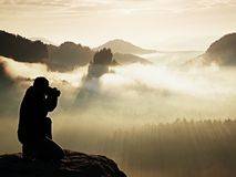 Professional photographer silhouette above a clouds sea, misty mountains Stock Photos