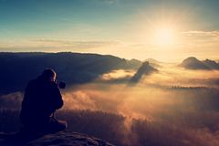 Professional photographer silhouette above a clouds sea, misty mountains Royalty Free Stock Image