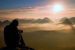 Professional photographer silhouette above a clouds sea, misty mountains Stock Image