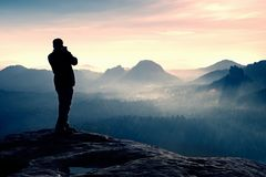 Professional photographer takes photos with big camera on rock. Dangerous possition at end of cliff.  Dreamy  foggy landscape, hot Stock Image