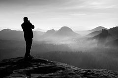 Professional photographer takes photos with big camera on rock. Dangerous possition at end of cliff.  Dreamy  foggy landscape, hot Stock Images