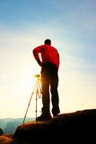 Professional photographer takes photos with camera on tripod on rocky peak. Dreamy spring landscape. Stock Photos