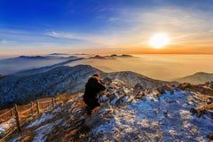 Professional photographer takes photos with camera on tripod. Royalty Free Stock Photo