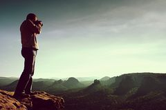 Professional photographer takes photos with mirror camera on cliff of rock. Dreamy misty landscape, hot Sun above Royalty Free Stock Images
