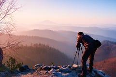 Professional photographer takes photos with mirror camera on peak of rock. Dreamy fogy landscape, spring orange pink misty sunrise Royalty Free Stock Image