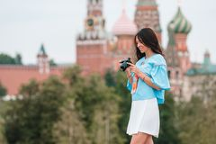 Professional photographer taking a city photo outdoors. Young woman taking a photo with camera of Red Square in Moscow royalty free stock images