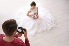 Professional photographer taking photo of beautiful bride in photo studio. Professional photographer taking photo of beautiful bride in studio Royalty Free Stock Images