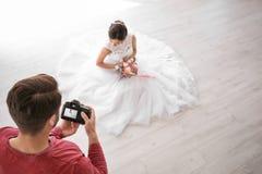 Professional photographer taking photo of beautiful bride in photo studio. Professional photographer taking photo of beautiful bride in studio Stock Image