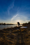 Professional photographer taking a photo flooding river. At sunset Royalty Free Stock Photos