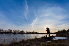 Professional photographer taking a photo flooding river. At sunset Stock Images