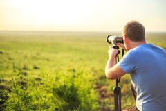 Professional photographer taking photo on savannah Stock Photography