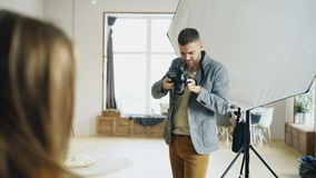 Professional photographer taking photos of model on digital camera working in photo studio. Indoors stock image