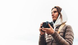 Professional photographer tourist traveler standing on on a white background holding in hands digital photo camera, hiker view fro. M front taking photography royalty free stock image