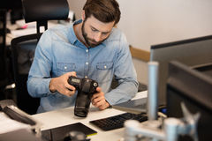 Professional photographer using camera in creative office. High angle view of professional photographer using camera in creative office stock photo