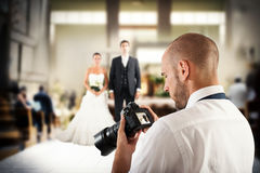 Professional photographer in a wedding. Photographer looks at the screen of camera to a wedding Stock Images