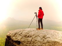 Professional photographer work on mountain peak. Nature photographer takes photos with mirror camera on rock. Above autumnal landscape. Dreamy fogy  valley Stock Photos