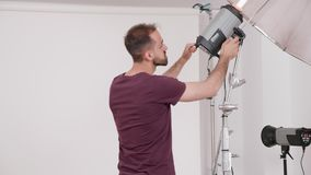 Professional photographer working and setting up the flashes before a fashion photo shoot. In the studio stock video footage
