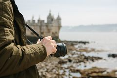 A professional photographer or a young male tourist photographes the sights in Lisbon in Portugal. Holds a camera. The. A professional photographer or a young Royalty Free Stock Image