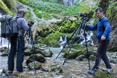 Professional photographers with cameras on tripods. Professional photographers with cameras on tripod shooting in a river Royalty Free Stock Images