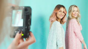 Professional photosession: two girls model posing on a turquoise stock video footage