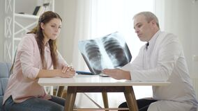 Professional physician explaining lungs x-ray to young woman in hospital. Side view portrait of mid-adult man and young