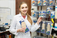 Professional physician offering orthopaedic insoles in special s. Young american professional physician offering orthopaedic insoles in special shop stock photo