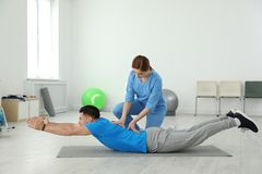 Professional physiotherapist working with male patient stock photo