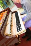 Professional piano technician removing keyboard for tuning repai. R. Determined repairman trying to tune and restore vintage musical instrument keyboard. Side Royalty Free Stock Photography